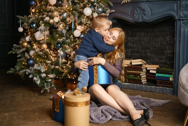 Mãe e filho sentado na pose de uma árvore de natal, conceito de férias.