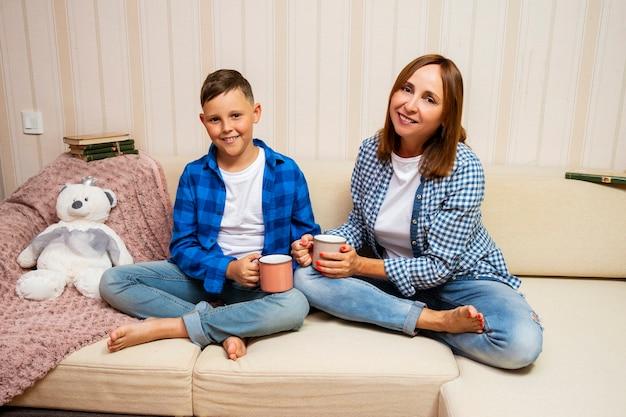 Mãe e filho sentado no sofá com uma xícara de chá. eles passam seu tempo livre juntos. mãe e filho felizes e se amam.