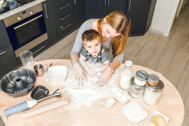 Mãe e filho sentados atrás da mesa da cozinha com coisas de cozinha nele. .