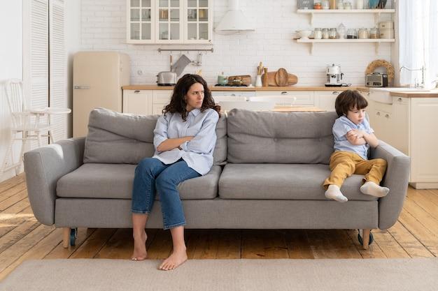 Mãe e filho sentados no sofá, ignorando-se, postura de descontentamento, não conversando após briga