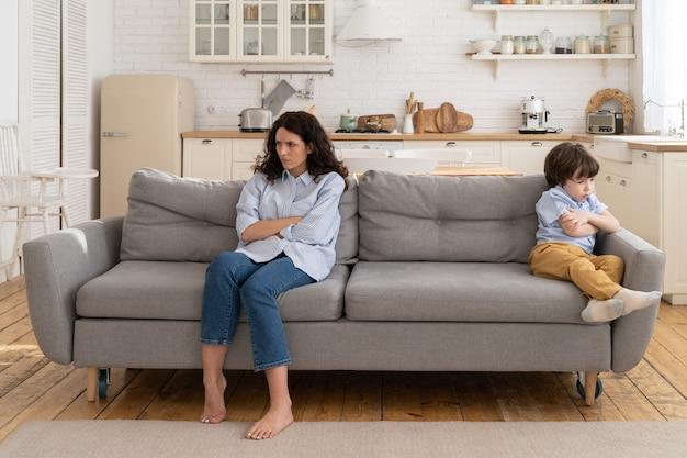 Mãe e filho sentados no sofá se ignorando