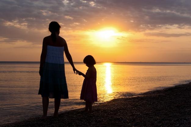 Mãe e filho silhuetas na praia do sol