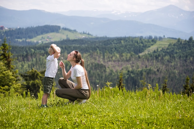 Mãe e filho soprar dente de leão floresta de coníferas e montanhas. maternidade e amizade