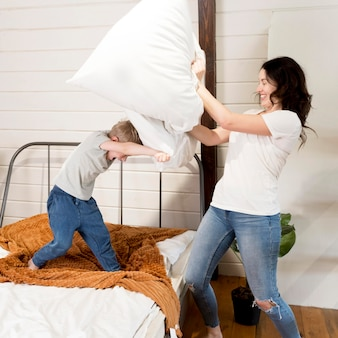 Mãe e filho tendo luta de almofadas