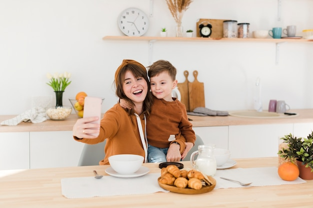 Mãe e filho tirando selfies na cozinha