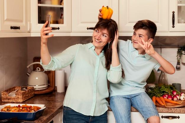 Mãe e filho tomando selfie na cozinha com legumes