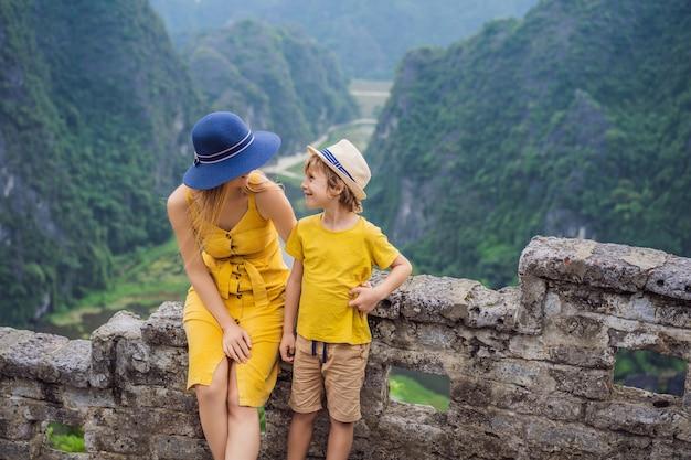 Mãe e filho turistas no lago tam coc e pagode do templo hang mua ninh binh vietnã seu é