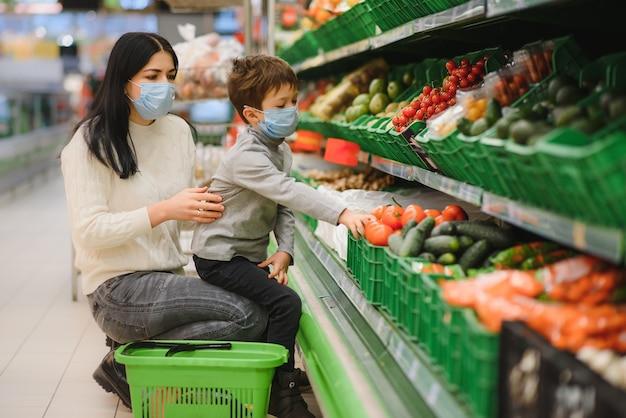 Mãe e filho usando máscaras protetoras escolhem frutas para comprar na loja