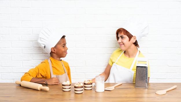 Mãe e filho vestido como chef em uma cozinha