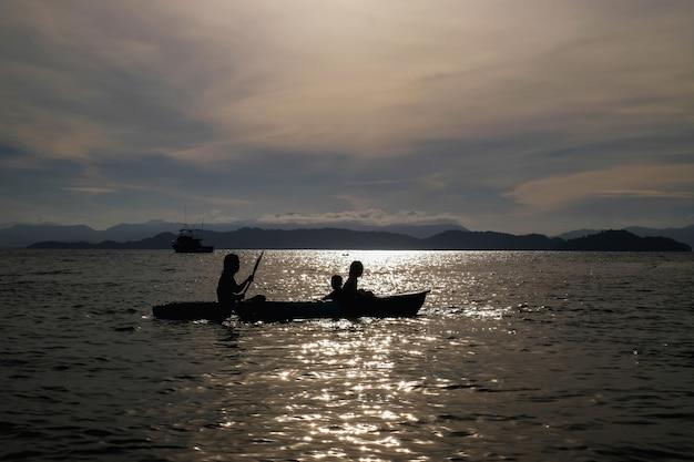Mãe e filhos a remo caiaque no mar em férias