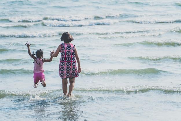 Mãe e filhos andando e runnes no mar ao pôr do sol