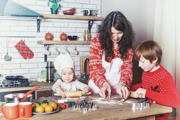 Mãe e filhos assam biscoitos na cozinha e decoram biscoitos na véspera de natal