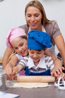 Mãe e filhos assando biscoitos na cozinha