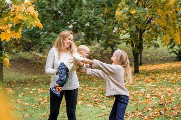Mãe e filhos brincando ao ar livre