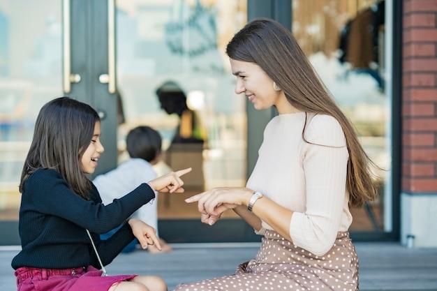 Mãe e filhos brincando com as mãos sorrindo ao ar livre