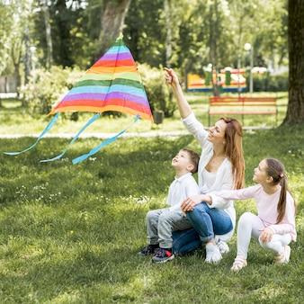 Mãe e filhos brincando com pipa