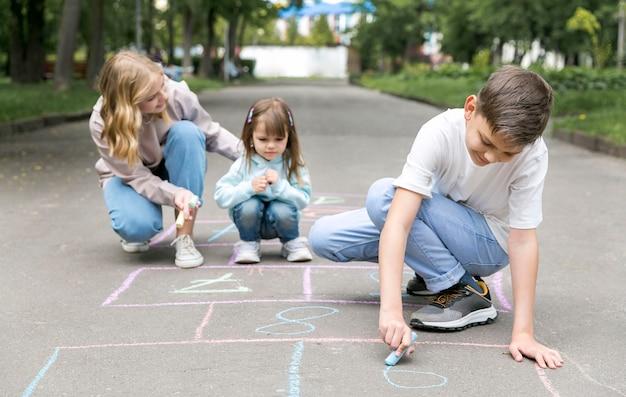 Mãe e filhos brincando de amarelinha