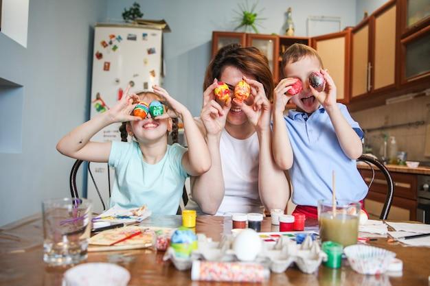 Mãe e filhos brincando experimentando ovos de páscoa pintados como olhos em casa na cozinha
