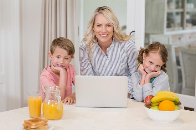 Mãe e filhos com laptop na cozinha