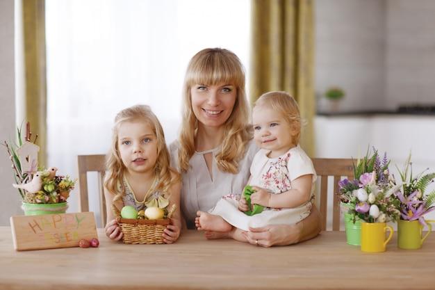 Mãe e filhos com ovos de páscoa coloridos na mesa de jantar