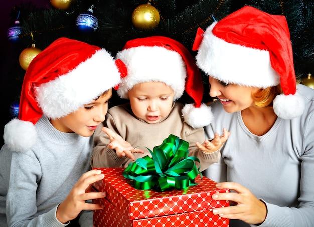 Mãe e filhos com presente de ano novo no feriado de natal esperando o milagre - dentro de casa