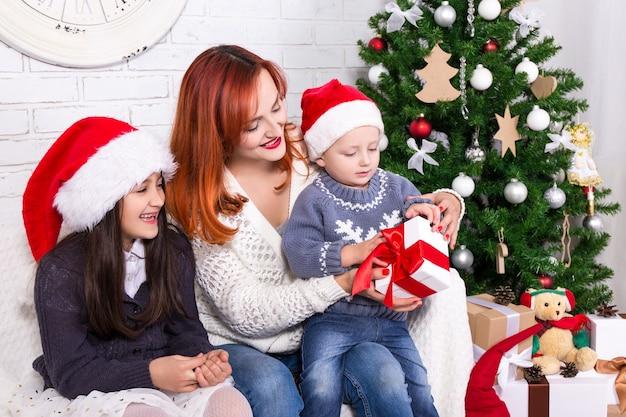 Mãe e filhos com presentes e árvore de natal