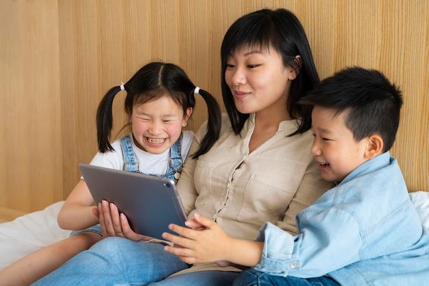 Mãe e filhos com tiro médio com tablet