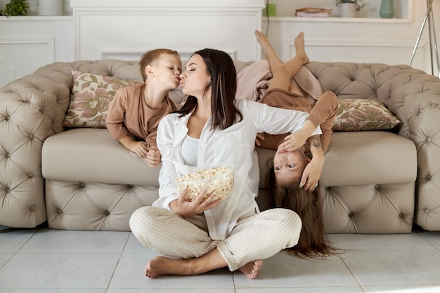 Mãe e filhos comem pipoca em casa em um dia de folga