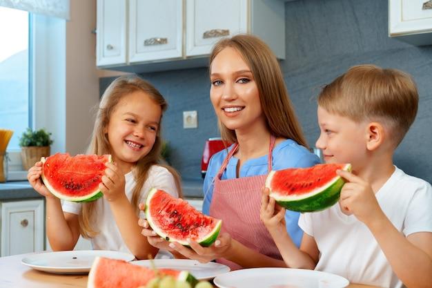 Mãe e filhos comendo melancia na cozinha