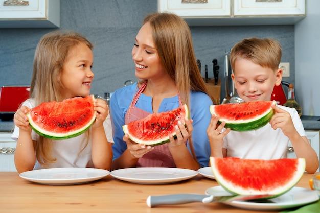 Mãe e filhos comendo melancia