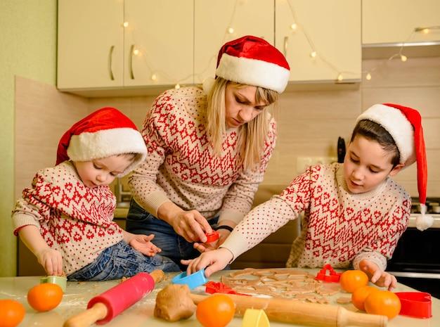 Mãe e filhos cozinhando biscoitos de natal em casa sobremesas saborosas