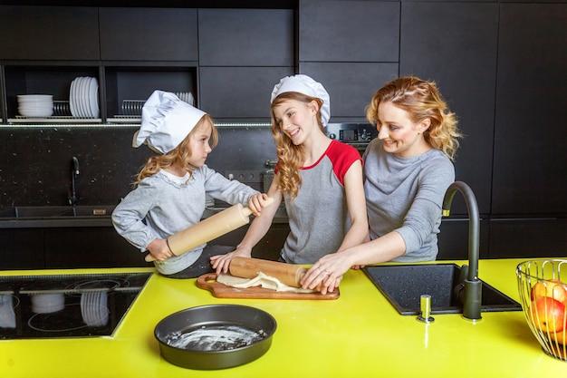 Mãe e filhos cozinhando na cozinha e se divertindo
