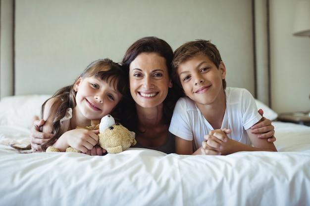 Mãe e filhos, deitada na cama com ursinho de pelúcia no quarto