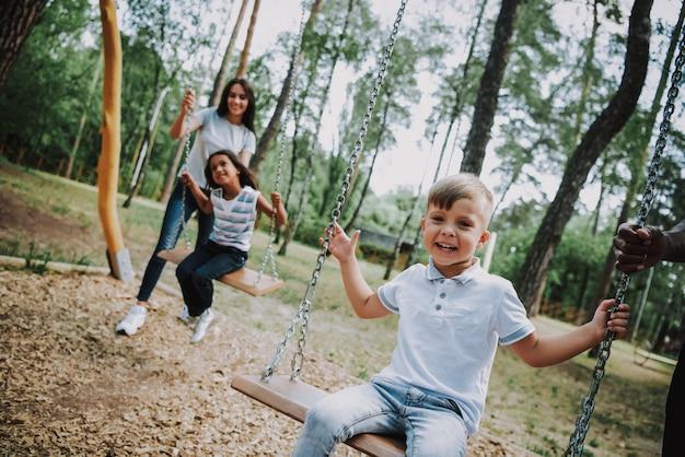 Mãe e filhos em fim de semana familiar de parque de diversões