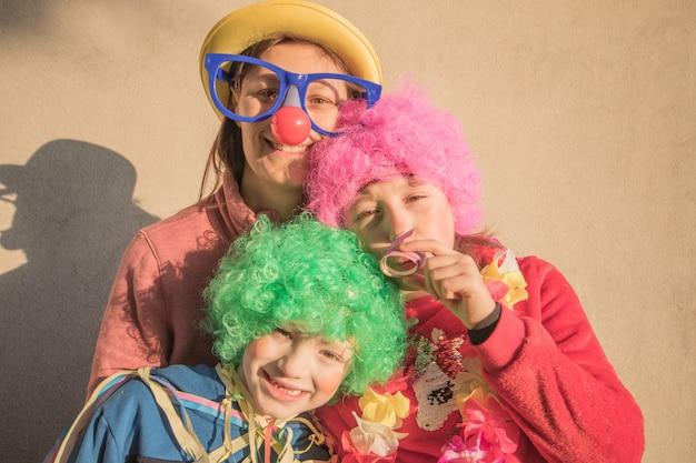 Mãe e filhos em máscara de carnaval sorrindo juntos ao ar livre