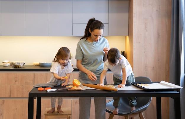 Mãe e filhos em tiro médio na cozinha
