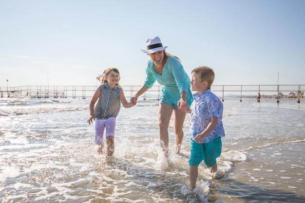 Mãe e filhos estão brincando no mar na praia