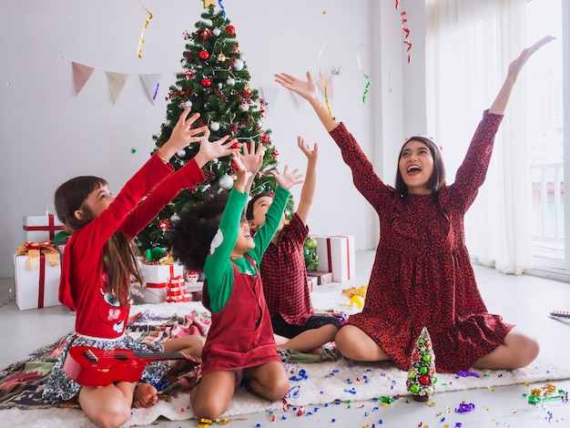 Mãe e filhos estão comemorando o natal e se divertindo e feliz em casa com árvore de natal