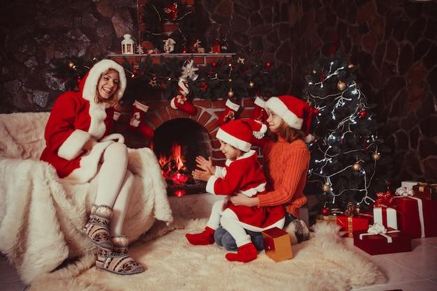 Mãe e filhos estão sentados perto da lareira e da árvore de natal com caixas de presente.