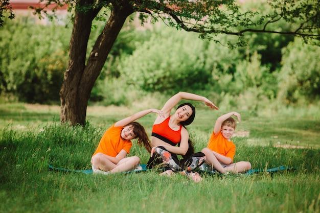 Mãe e filhos fazem esportes ao ar livre. estilo de vida saudável e treinamento físico.