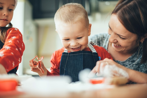 Mãe e filhos fazendo biscoitos para o natal em casa vestindo roupas de papai noel vermelho e sorrindo