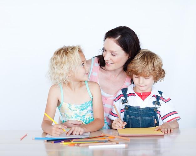 Mãe e filhos fazendo lição de casa juntos