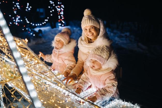 Mãe e filhos na cidade à noite com luzes de natal à noite