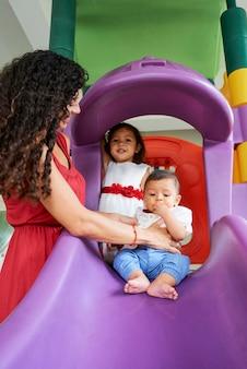 Mãe e filhos no parque infantil
