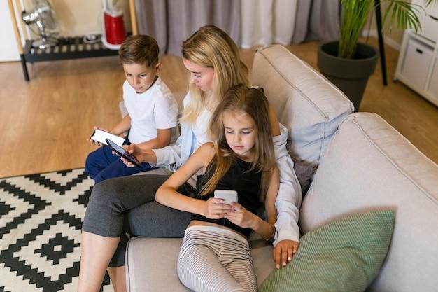 Mãe e filhos olhando para seus telefones
