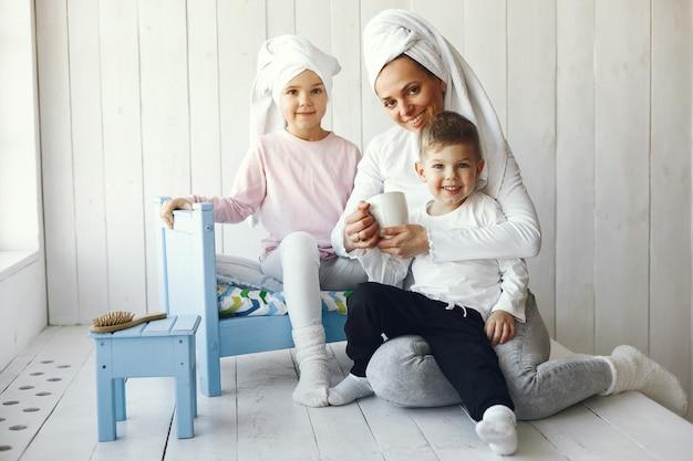 Mãe e filhos pequenos se divertem em casa
