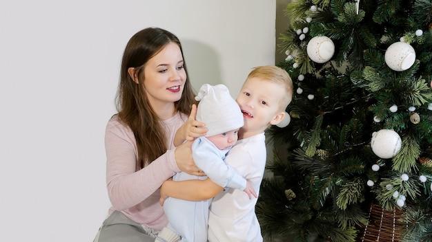 Mãe e filhos perto da árvore de natal