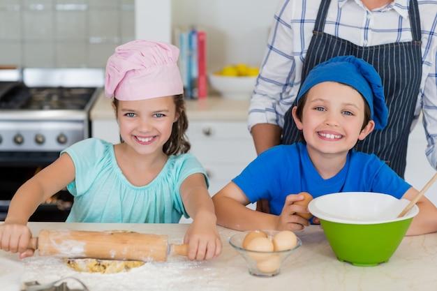 Mãe e filhos preparando comida na cozinha