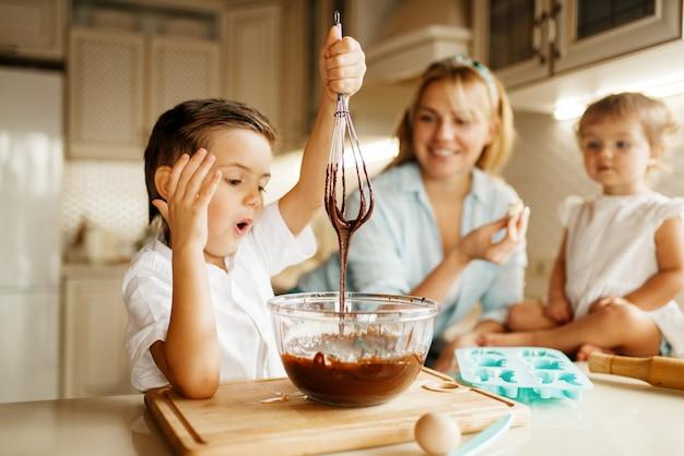 Mãe e filhos provam chocolate derretido