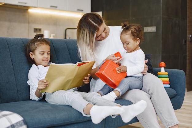 Mãe e filhos relaxando juntos no sofá da sala de estar em casa. meninas brincando com brinquedos e lendo um livro.